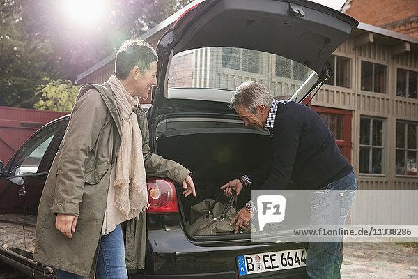 Glückliche Frau schaut den Mann an  der die Tasche in den Kofferraum steckt.