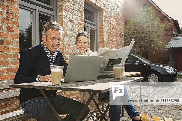 Reifer Mann mit Laptop und Frau mit Zeitung im Hinterhof