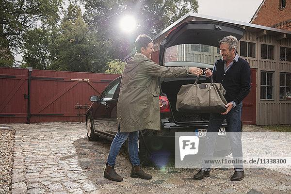 Glückliche Frau  die dem Mann mit dem Auto auf der Einfahrt eine Tasche schenkt.