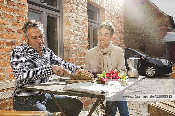 Frau schaut den Mann an  der im Garten Brot schneidet.