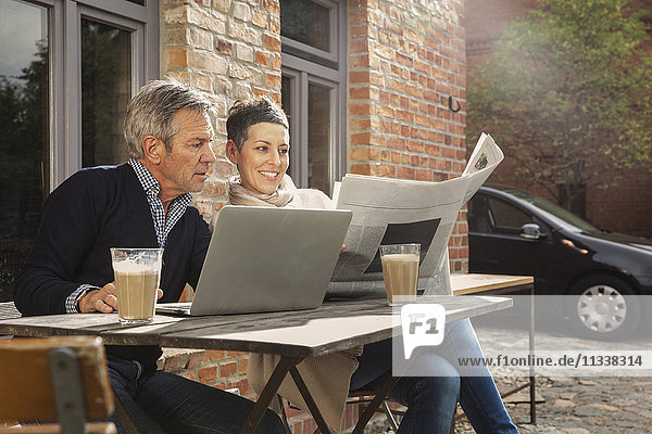Reife Männer und Frauen beim Zeitungslesen mit Laptop im Hinterhof