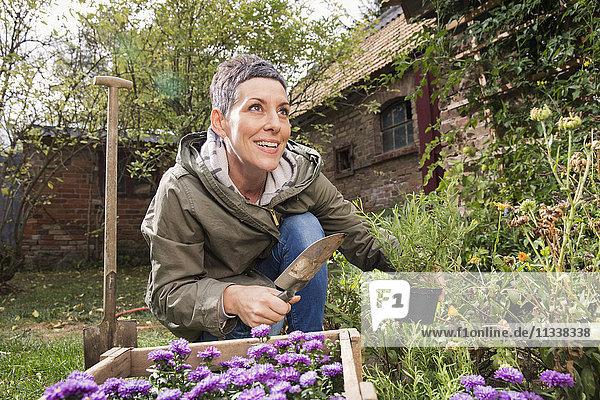 Glückliche Frau mit Kelle und Topfpflanze im Garten