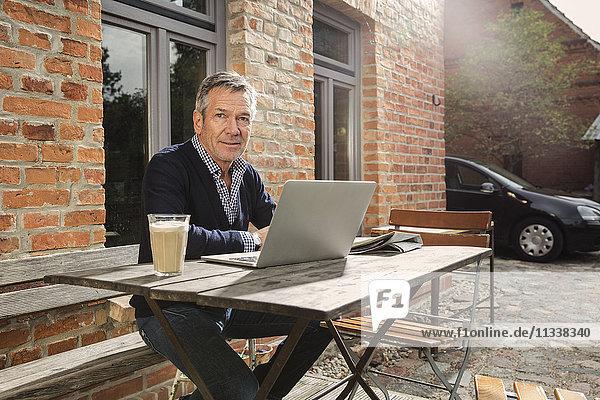 Porträt eines reifen Mannes mit Laptop im Hinterhof