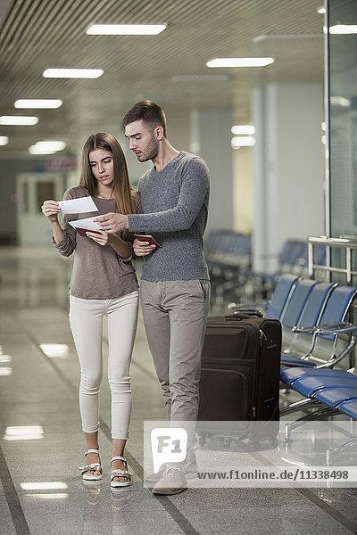 Volle Länge der Lesekarten für junge Paare am Flughafen