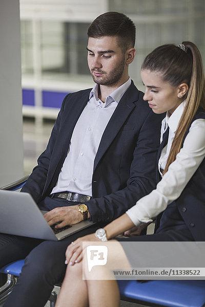 Junge Geschäftsfrau sitzend von Geschäftsmann mit Laptop am Flughafen