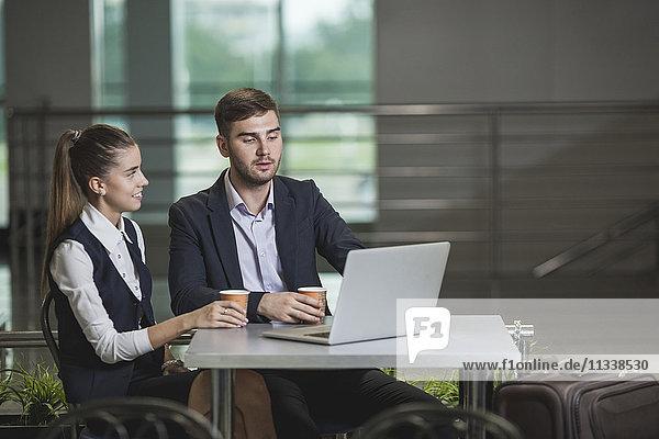 Junger Geschäftsmann mit Kollegin am Tisch des Flughafens mit Laptop
