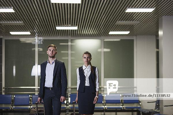 Porträt eines selbstbewussten Jungunternehmers und Geschäftsfrau mit Gepäck am Flughafen