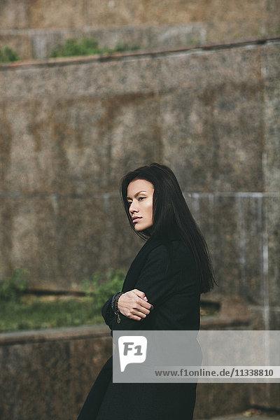 Seitenansicht der einsamen Frau  die weg schaut  während sie die Arme gegen die Wand kreuzt.