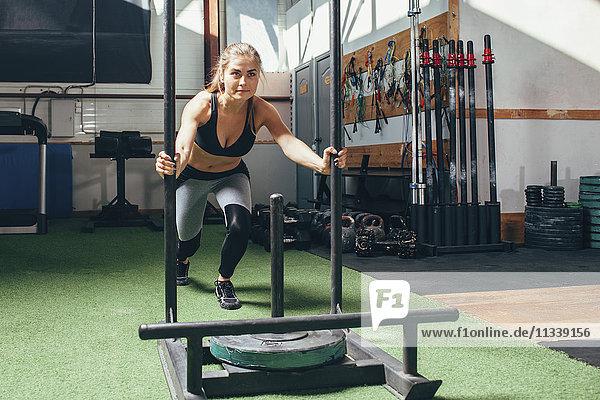 Entschlossene Frau beim Schlittenschieben im Fitnessstudio