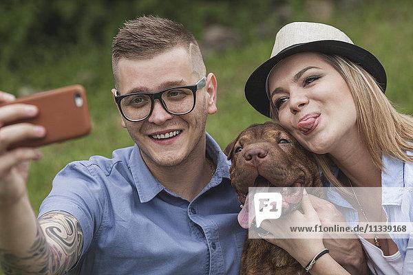 Ein Paar mit ihrem Shar-pei/Staffordshire Terrier im Park mit einem Selfie.