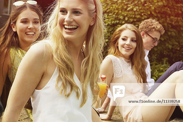 Fröhliche Frau sitzt mit Freunden auf dem Hof