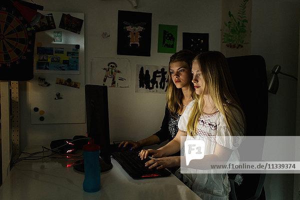 Teenager-Mädchen mit Computer in der Dunkelkammer zu Hause