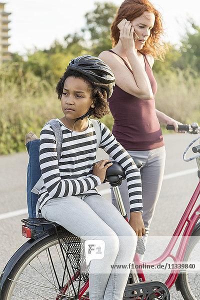 Mädchen sitzt auf dem Fahrrad  während die Mutter auf dem Handy spricht.