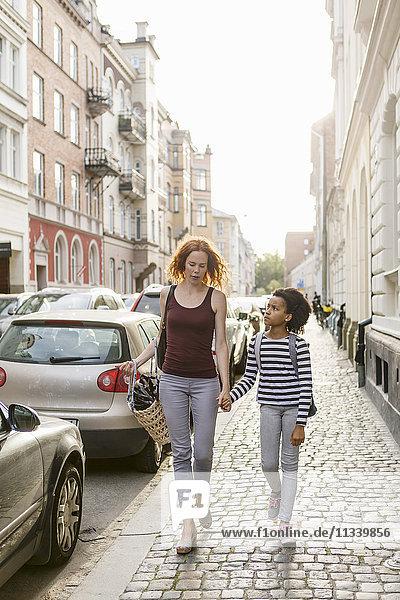 Mädchen schaut Mutter an  während sie in der Stadt auf dem Bürgersteig geht.