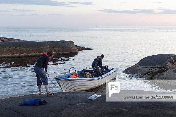 Rückansicht der Frau  die das Seil hält  während sie mit Mann und Tochter im Motorboot auf einer Felsformation steht.