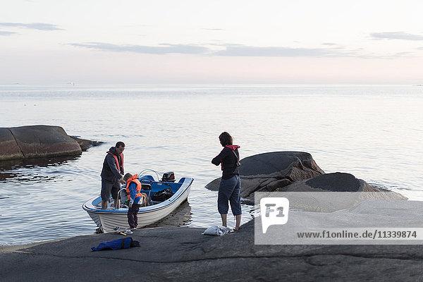 Familienstand mit Motorboot in der Ostsee gegen den Himmel bei Sonnenuntergang