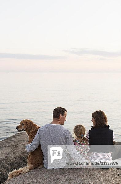 Rückansicht der Familie sitzend mit Hund auf Felsformation gegen den Himmel