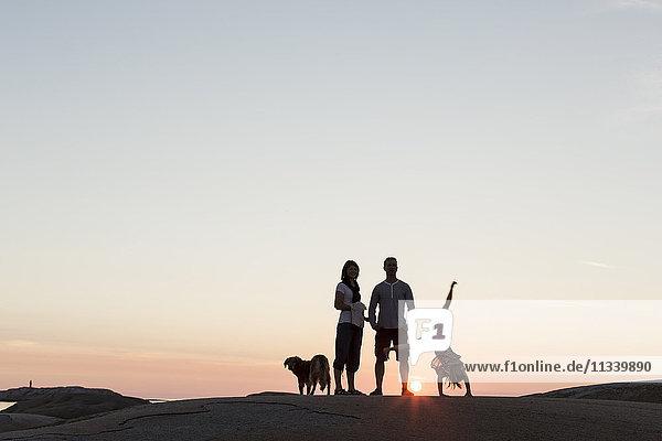 Vater und Mutter beim Anblick eines Mädchens  das bei Sonnenuntergang auf einer Felsformation gegen den Himmel fährt.