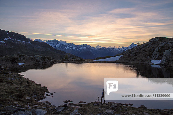 Photographer admires the pink sunrise on Lake Zana  Malenco Valley  Valtellina  Province of Sondrio  Lombardy  Italy  Europe