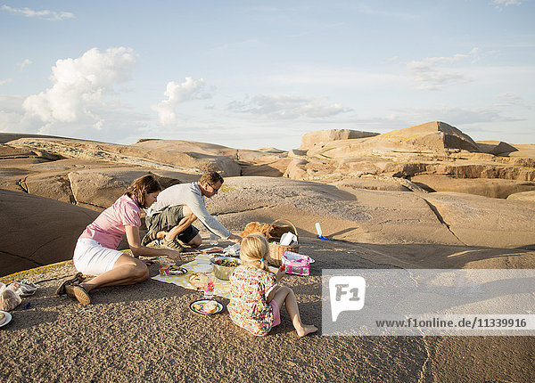 Family enjoying picnic on rock formation against sky