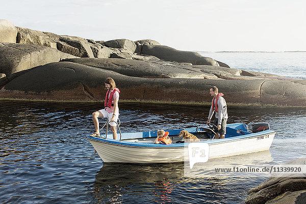 Familie und Hund auf dem Motorboot in der Ostsee inmitten von Felsformationen
