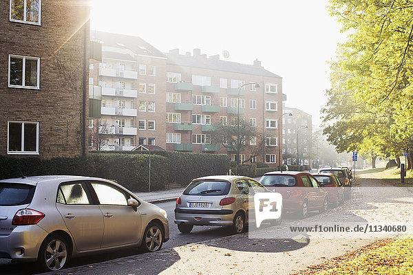 Autos am Straßenrand gegen Mehrfamilienhäuser geparkt