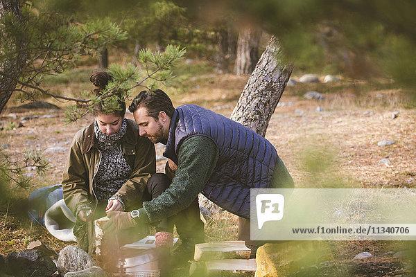 Pärchen mit Brennholz auf dem Campingplatz