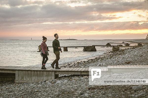 Seitenansicht des Paares  das bei Sonnenuntergang am Strand gegen den Himmel läuft.