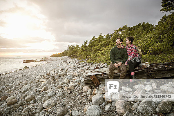 Paar auf Holz am Strand gegen den Himmel sitzend