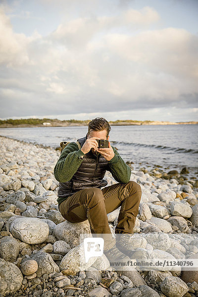 Man photographing from camera while sitting on rock at beach against sky