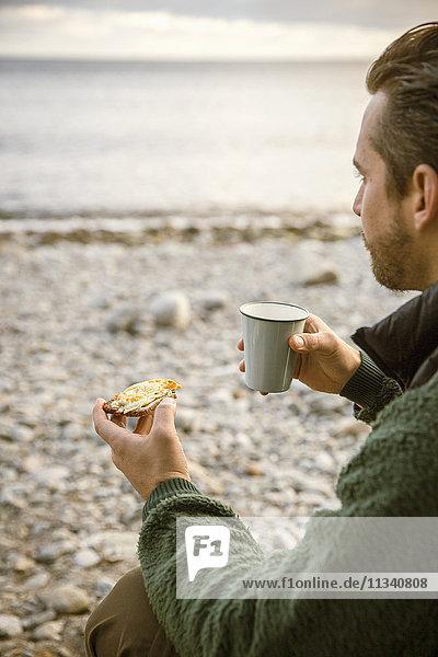 Abgeschnittenes Bild eines Mannes  der einen Snack mit Kaffee am Strand isst.