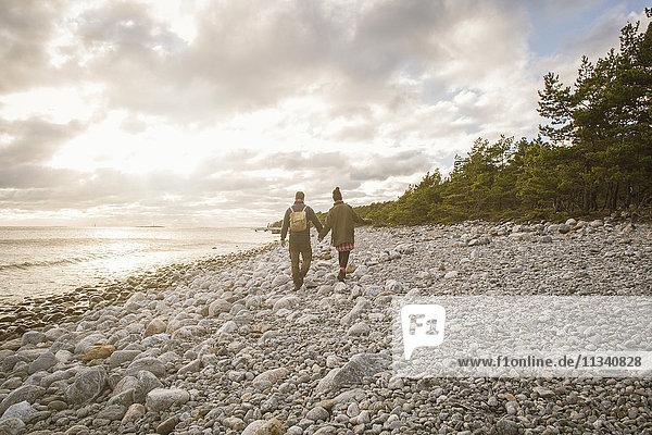 Rückansicht des Paares  das bei Sonnenuntergang am felsigen Ufer gegen den Himmel läuft.