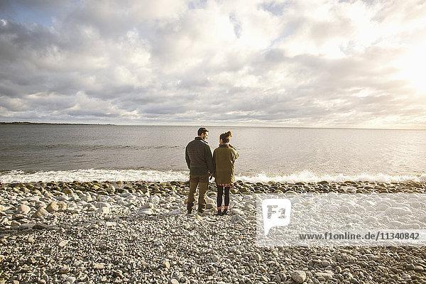 Rückansicht des Paares  das am felsigen Ufer am Strand gegen den Himmel steht.