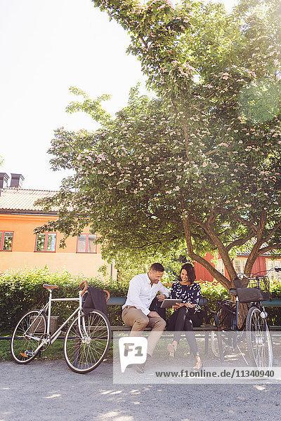 Geschäftsleute  die ein digitales Tablett benutzen  während sie mit dem Fahrrad auf der Bank sitzen.