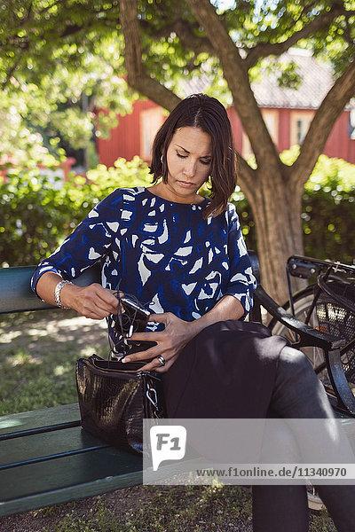 Geschäftsfrau nimmt In-Ear-Kopfhörer aus dem Portemonnaie und sitzt auf der Parkbank.