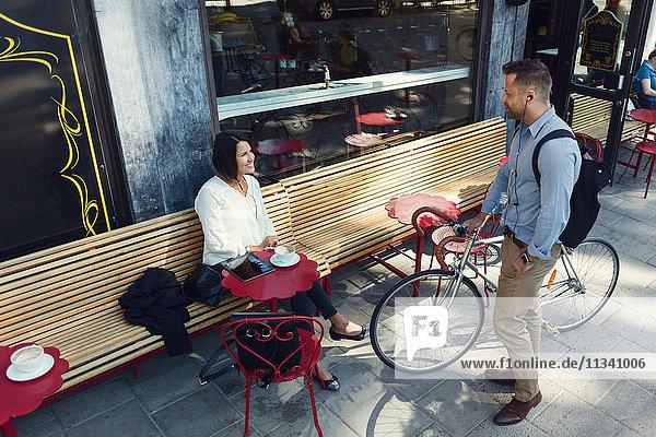 Geschäftsmann mit Fahrrad im Gespräch mit einer Kollegin  die im Straßencafé sitzt.