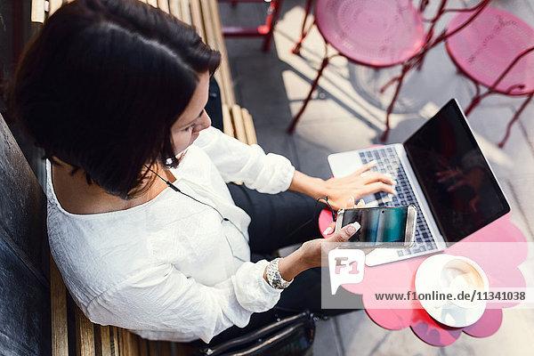 Hochwinkelansicht der Geschäftsfrau mit Smartphone und Laptop im Bürgersteigcafe