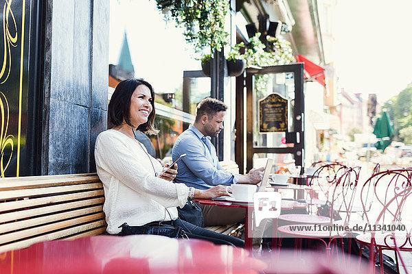 Nachdenkliche Geschäftsfrau  die ein Smartphone hält  während sie im Café sitzt.