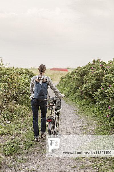Rückansicht einer Frau  die einen Rucksack trägt und mit dem Fahrrad auf einem Wanderweg inmitten von Pflanzen wandert.