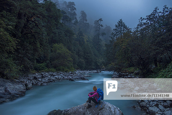 A woman takes a break from the trail and sits beside the Langtang Khola near the little village of Riverside on a misty evening  Nepal  Himalayas  Asia
