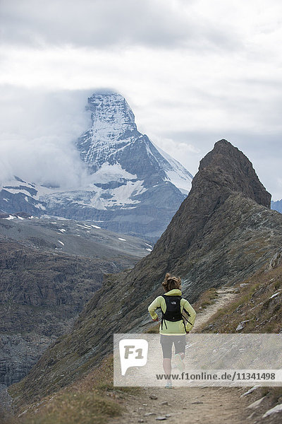 Running a trail in the Swiss Alps near Zermatt with a view of The Matterhorn in the distance  Zermatt  Valais  Switzerland  Europe