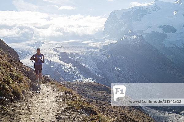 Running a trail in the Swiss Alps near Zermatt with a view of Monte Rosa in the distance  Zermatt  Valais  Switzerland  Europe