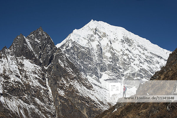 A woman trekking up Kyanjin Ri in the Langtang Valley with a view of Langtang Lirung in the distance  Langtang Region  Himalayas  Nepal  Asia