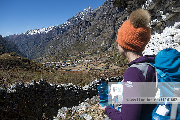 A woman trekking in the Langtang valley in Nepal rests near a chorten  Langtang Region  Himalayas  Nepal  Asia
