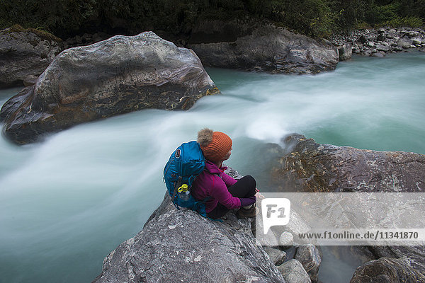 A woman takes a break from the trail and sits beside the Langtang Khola near the little village of Riverside on a misty evening  Langtang Region  Nepal  Asia