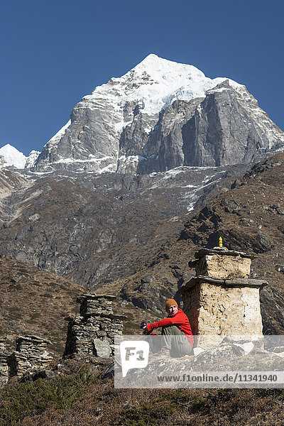 A trekker stops beside a chorten to admire the views on the way to Everest Base Camp with views of Taboche in the distance  Khumbu Region  Himalayas  Nepal  Asia