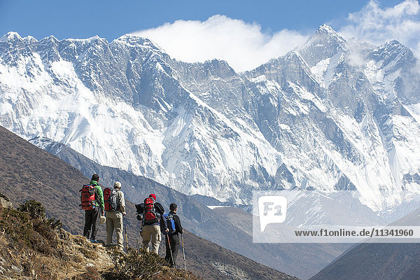 Trekkers look up at Everest  the distant peak on the left  with Nuptse and Lhotse  Khumbu Region  Himalayas  Nepal  Asia