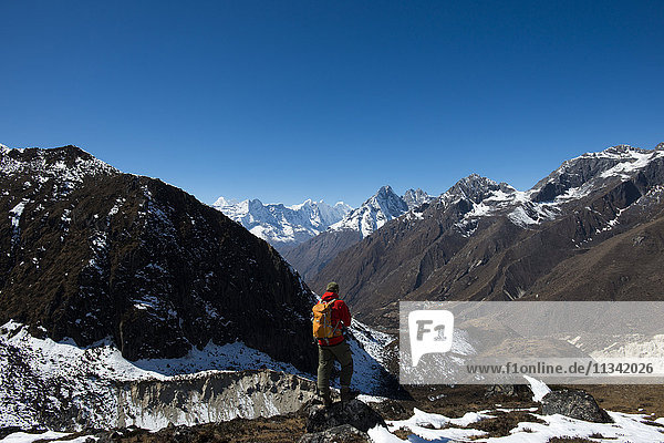 A trekker in the Everest region looks down on the Khumbu Valley towards Pangboche  Khumbu Region  Himalayas  Nepal  Asia