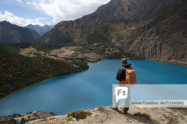 A trekker looks out at the turquoise blue Phoksundo Lake  Dolpa Region  Himalayas  Nepal  Asia