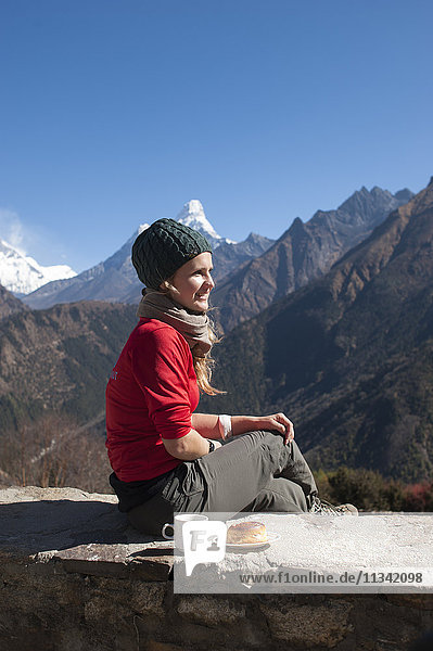 A trekker stops on the trail for some fuel  with Ama Dablam is the peak visible in the distance  Khumbu Region  Nepal  Asia